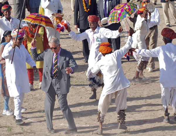 Britain's Prince Charles dances with villagers at Tolasar village