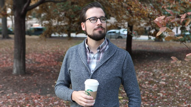 Mr. Autumn Man Walking Down Street With Cup Of Coffee, Wearing Sweater Over Plaid Collared Shirt