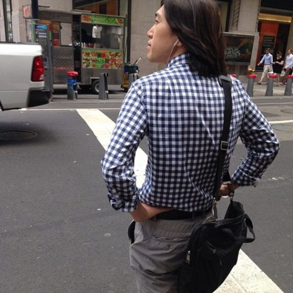 Spring Man Walking Down Street with Shoulder Bag, Wearing Gingham Shirt and Flat Front Chinos